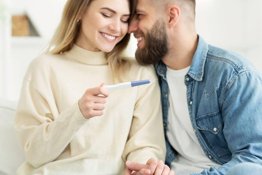 Foto de pareja felices con prueba de embarazo